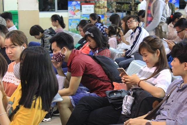 Nhiều người mệt mỏi ngồi chờ trong bến xe đợi để mua vé.
