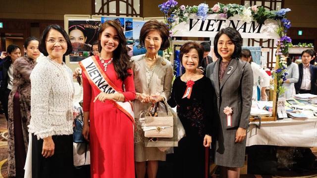 Nguyễn Quỳnh Anh mặc áo dài đỏ đại diện cho gian hàng Việt Nam tại hội chợ từ thiện lớn nhất năm của Hội Phụ nữ Châu Á - Thái Bình Dương.