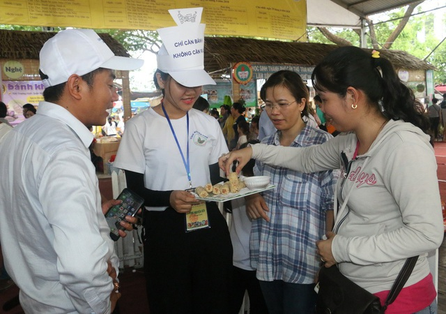 Các tình nguyện viện mời du khách thưởng thức bánh dân gian