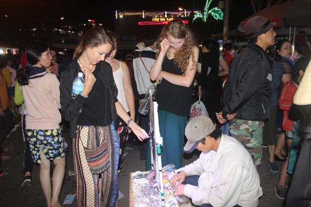 Ba vị khách nước ngoài đang lựa chọn mua những món đồ lưu niệm tại chợ đêm Đà Lạt