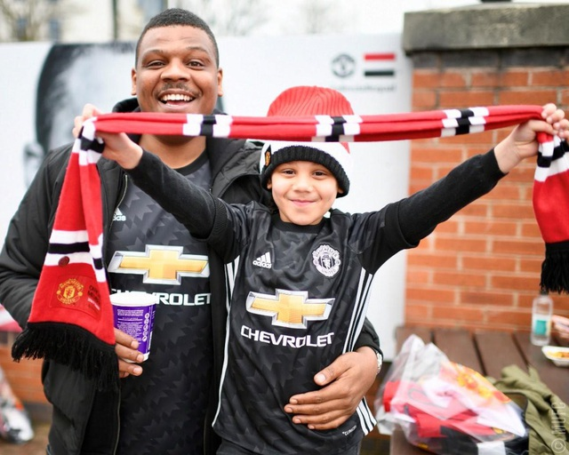 Cổ động viên nhí của MU khoe tấm khăn lưu niệm trước cửa sân Old Trafford