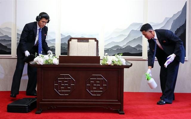 Các vệ sĩ Triều Tiên tẩy trùng sàn nhà và bàn ghế trước khi nhà lãnh đạo Kim Jong-un ngồi viết vào sổ lưu niệm tại Nhà Hòa bình ở khu phi quân sự liên Triều.