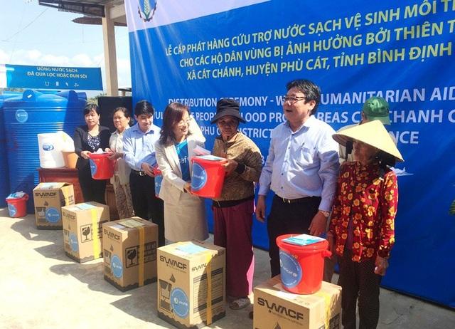 Người dân xã Cát Chánh phấn khởi khi nhận hàng cứu trợ.