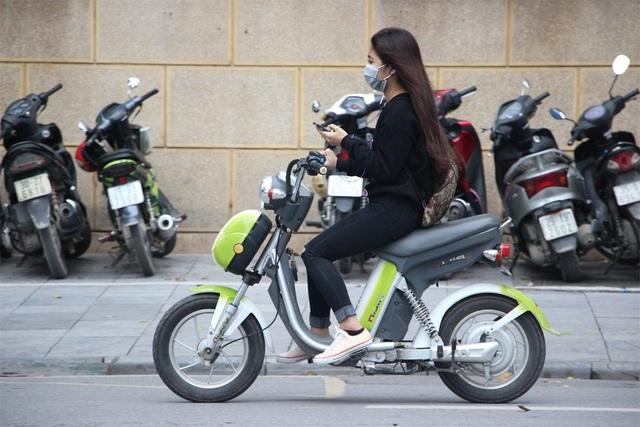 Học sinh Hà Nội vừa đi xe máy điện vừa sử dụng điện thoại rất nguy hiểm (Ảnh: Nguyễn Dương)