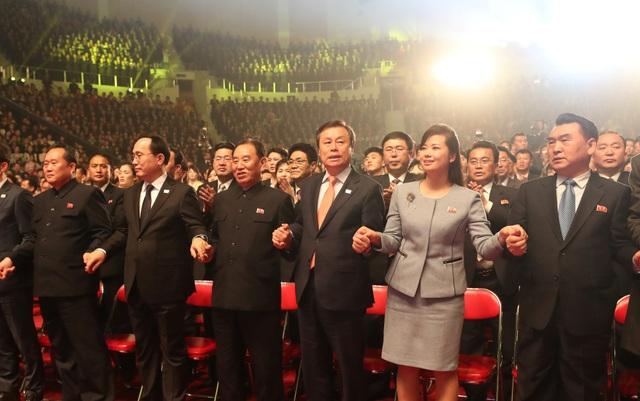 Phó chủ tịch đảng Lao động Triều Tiên Kim Yong Chol (thứ 4 từ phải sang), Bộ trưởng Văn hóa Hàn Quốc Do Jong-hwan (thứ 3 từ phải sang) và trưởng đoàn nghệ thuật Samjiyon Hyon Song Wol (thứ hai từ phải sang) nắm tay nhau khi theo dõi các tiết mục của các nghệ sĩ trên sân khấu. (Ảnh: Reuters)