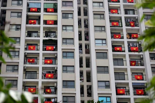 Cờ đỏ sao vàng treo trước ban công các căn hộ chung cư tạo cảnh tượng khá lạ mắt.