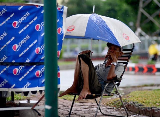 Ông cụ sửa xe ngồi co ro dưới chiếc dù trên vỉa hè.