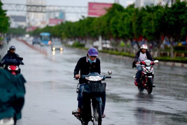 Thanh niên đi xe máy khép mình vì không có áo mưa.