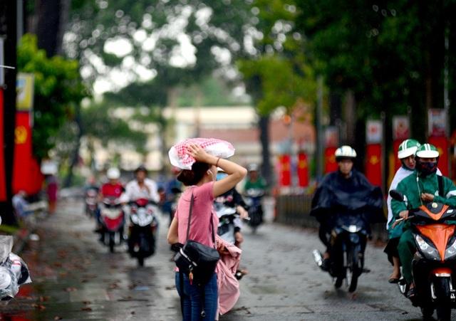 Cô gái dùng túi nilon che đầu đi qua đường.