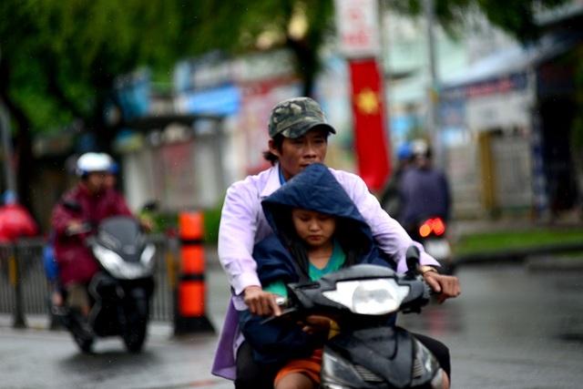 Người cha nhường chiếc áo mưa cho cậu con trai.