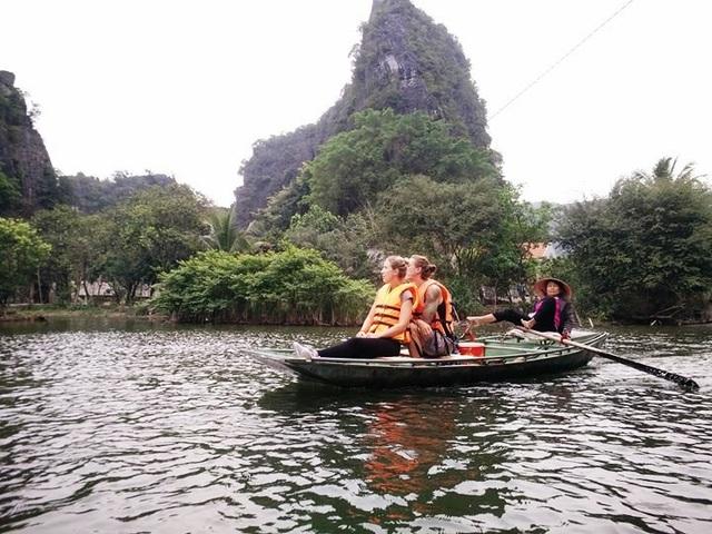Bằng đôi chân, người chở đò ở Tam Cốc điều khiển chiếc thuyền lao đi vun vút khắp các điểm tham quan.