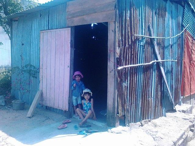 Hai đứa trẻ khắc khoải mong chờ tin cha bên căn nhà tôn che tạm