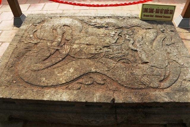 Trên mặt sập đá chạm khắc nổi hình con rồng đang cuộn mình với thế uy quyền của bậc đế vương. Cũng trên mặt sập đá, một hình sư tử được khắc sắc nét giữa hai chi sau của con rồng. Đầu rồng to, miệng đang há ngậm viên ngọc, răng và sừng sắc nhọn... Đặc biệt, bốn chi của rồng được nhân cách hóa, theo đó, thay vào chi chim ưng với những móng vuốt sắc nhọn thì chi rồng này là 4 bàn tay người phụ nữ mềm mại, tay thì cầm sừng và bờm, tay thì vít râu rồng...