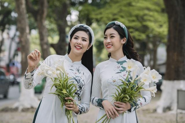 Trước ống kính, Ngọc Hân và Đỗ Mỹ Linh đã diện những thiết kế áo dài hoạ tiết hoa loa kèn dạo bước trên đường phố Hà Nội. Cả hai nàng Hậu đều trang điểm nhẹ nhàng, khoe nụ cười toả nắng khi sóng bước bên nhau.