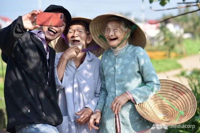 Cụ So và cụ Loi chụp ảnh tự sướng với khách du lịch. (Ảnh: Mediacorp)