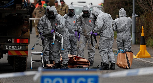 Các nhân viên quân sự Anh mặc đồ bảo hộ khi vận chuyển một phương tiện liên quan tới vụ cựu điệp viên Nga nghi bị đầu độc tại Anh (Ảnh: AFP)