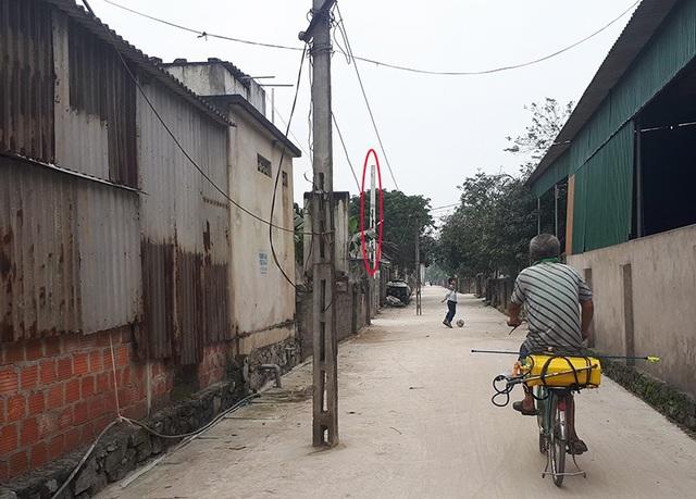 Cột điện mới (khoanh đỏ) đã được trồng khá lâu nhưng đường dây vẫn chưa được chuyển sang để di dời những cái bẫy chình ình giữa đường.