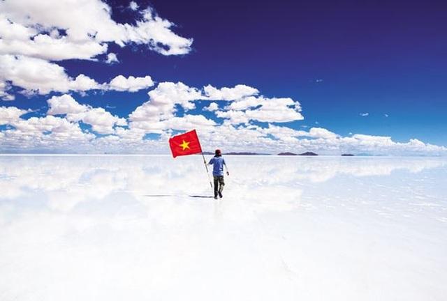 Anh Nguyễn Hoàng Bảo cầm cờ Tổ quốc tại cánh đồng muối Uyuni de Salar ở Bolivia. Ảnh: NVCC.