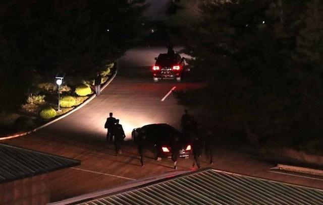 12 vệ sĩ vẫn chạy bộ theo xe ông Kim khi rời hội nghị lúc tối trời. Ảnh: Reuters