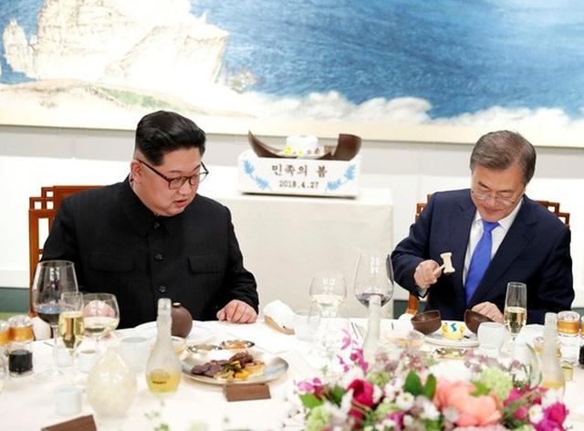Ông Kim học cách ăn món tráng miệng cầu kỳ. Ảnh: Reuters