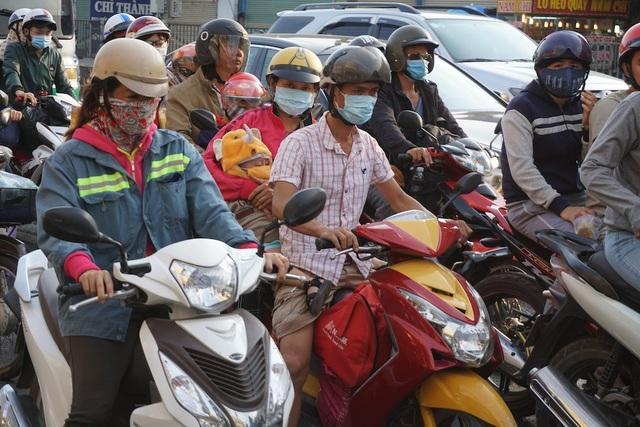 Nhiều người chạy xe máy bồng bế con nhỏ, vất vả trở lại Sài Gòn