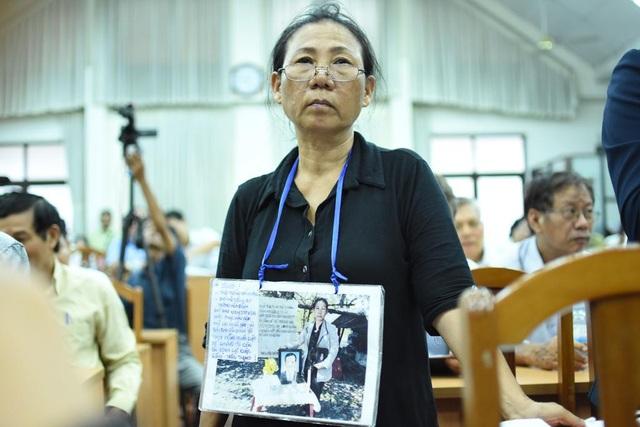 Bà Phượng đeo bức ảnh chụp phí trước căn chòi, trên nền nhà cũ bên di ảnh người chồng đã mất vì sốc khi bị thu hồi đất
