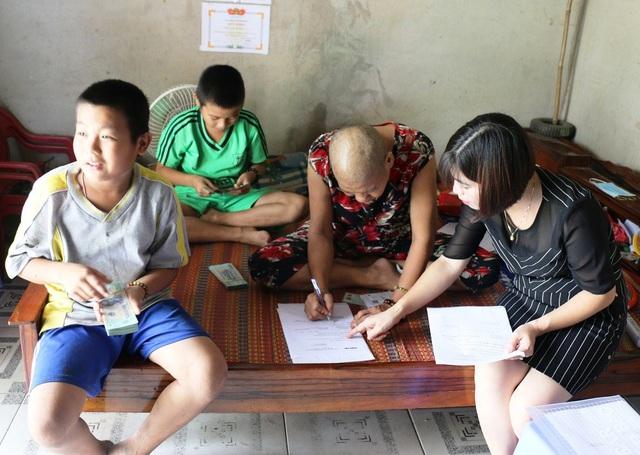 Bà Ngon ký nhận tiền, còn các con vui vẻ giành nhau đếm tiền