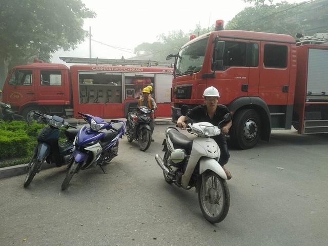 Nhiều công nhân di chuyển xe máy ra khỏi khu vực cháy.