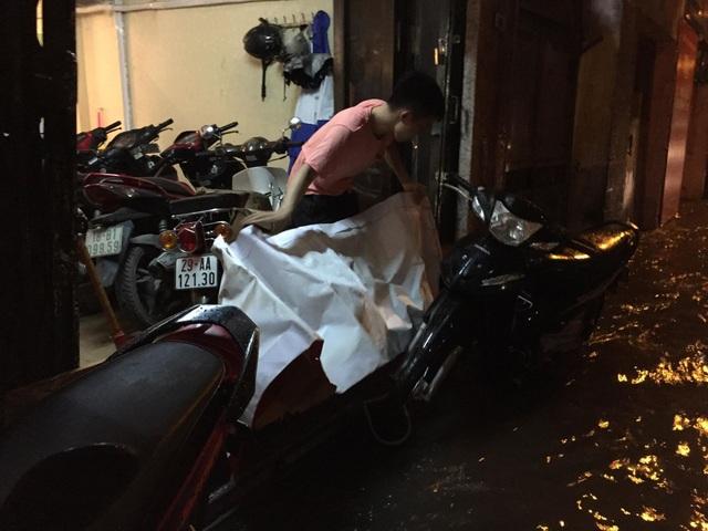 Người dân dùng các vật dụng để chắn nước khỏi vào nhà trong phố Chính Kinh