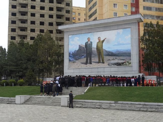 Người dân Triều Tiên tỏ lòng thành kính trước bức họa hai cố lãnh đạo (Ảnh: Rachel Davey)