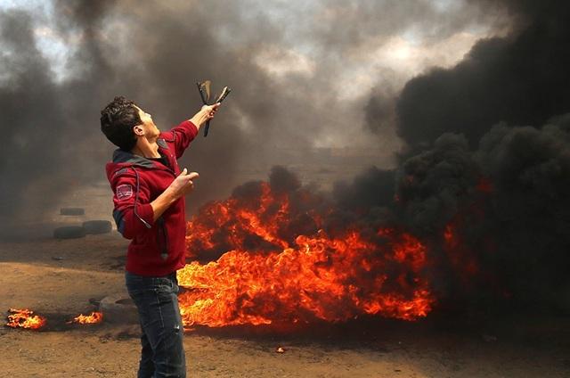 Phía quân đội Israel cho biết có khoảng gần 10.000 người biểu tình tập trung ở đường biên giới khu vực Dải Gaza và hàng nghìn người khác tụ tập ở khu vực trong bán kính 0,5 km so với hàng rào an ninh trong vụ đụng độ ngày 14/5. Trong ảnh: Người biểu tình Palestine đối đầu với lực lượng Israel tại Dải Gaza. (Ảnh: AFP)