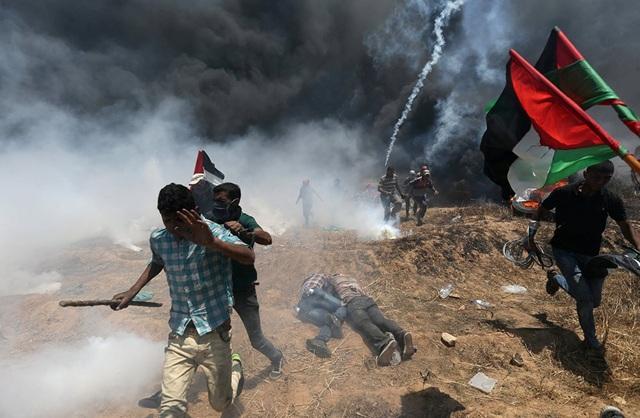 Vào thời điểm Mỹ khánh thành đại sứ quán mới tại Jerusalem, xung đột đẫm máu giữa lực lượng an ninh Israel và người biểu tình Palestine đã nổ ra tại dải Gaza. Trong ảnh: Người Palestine chạy tìm nơi trú ẩn trong vụ đụng độ với lực lượng Israel hôm 14/5. (Ảnh: Reuters)