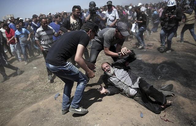 Ít nhất 55 người Palestine, trong đó có 6 trẻ em dưới 18 tuổi, đã thiệt mạng trong vụ bạo lực với Israel tại dải Gaza đúng vào ngày Mỹ chính thức chuyển đại sứ quán từ Tel Aviv về Jerusalem. Trong ảnh: Người đàn ông Palestine ngã quỵ sau khi bị lính Israel bắn tại Dải Gaza hôm 14/5. (Ảnh: AFP)