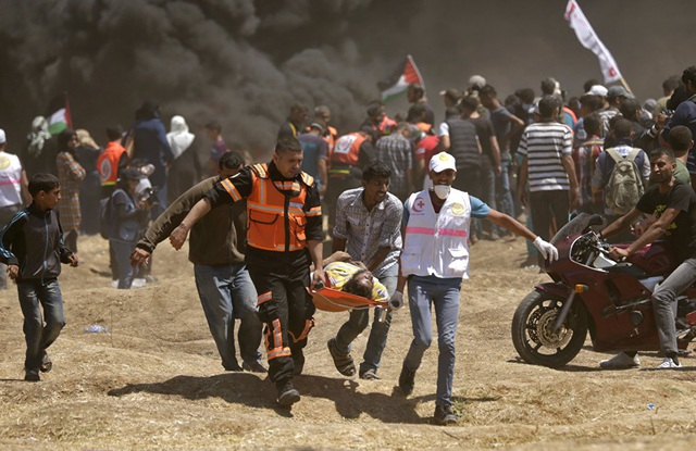 Ngày 14/5 cũng là ngày đẫm máu nhất với số người chết nhiều nhất trong lịch sử cuộc xung đột giữa Palestine và Israel kể từ sau cuộc chiến Dải Gaza năm 2014. Trong ảnh: Nhân viên y tế Palestine khiêng một người biểu tình bị thương tại Dải Gaza. (Ảnh: AFP)