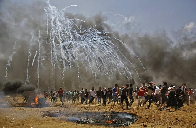 """Ngoài 55 người thiệt mạng, hơn 2.000 cũng bị thương trong vụ đụng độ ở khu vực Gaza giữa Israel và Palestine. Tổng thống Palestine Mahmoud Abbas đã lên án Israel, kêu gọi cộng đồng quốc tế nhanh chóng hành động chống lại """"những vụ thảm sát nhằm vào người dân ôn hòa"""" của Palestine. Trong ảnh: Người Palestine đồng loạt bỏ chạy trong cuộc xung đột với lực lượng an ninh Israel. (Ảnh: AFP)"""
