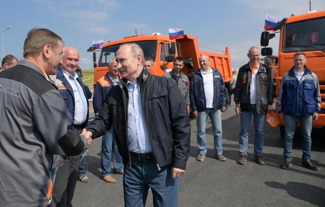 Sau khi nói lời cảm ơn và bắt tay những người đứng đầu các nhóm tham gia xây dựng cây cầu, Tổng thống Putin đã ngồi vào ghế lái của một xe tải màu cam để di chuyển qua cây cầu.