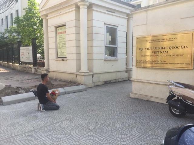 Chàng trai ôm hoa quỳ đợi cô gái tên Mai trước cổng Học viện Âm nhạc quốc gia Việt Nam (Ảnh: Ngọc Lâm)