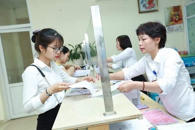 Cán bộ UBND phường Thịnh Quang (Hà Nội) làm việc tại bộ phận một cửa. Hiện tại, đội ngũ công chức vẫn chưa thể sống được bằng lương. Ảnh: HẢI NGUYỄN