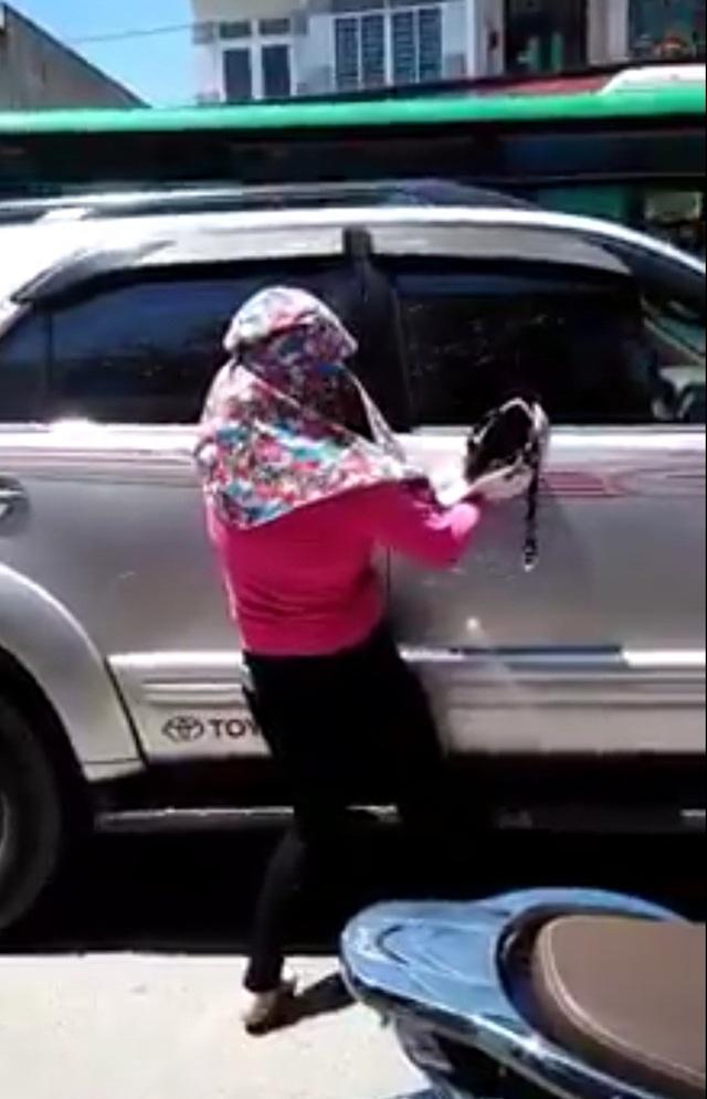 Một phụ nữ bám vào thân xe, dùng mũ bảo hiểm đập cửa liên hồi. (Ảnh cắt từ clip)