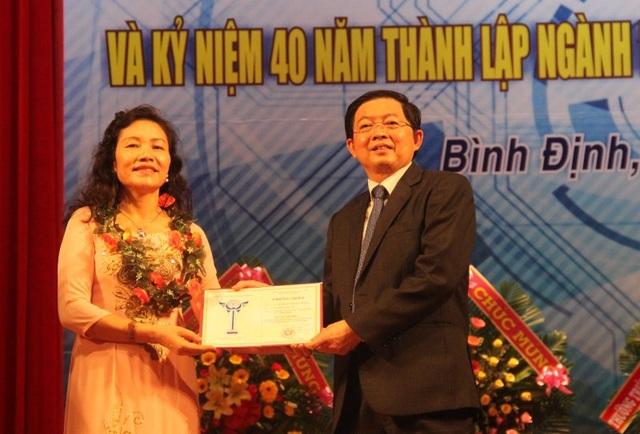 Chủ tịch UBND tỉnh Bình Định trao giấy chứng nhận cho những trí thức có đóng góp lớn về nghiên cứu khoa học.