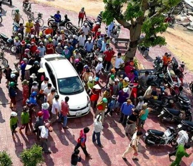 Người dân nghi ngờ đôi nam nữ đi ô tô bắt cóc trẻ em nên vây kín đòi đánh (ảnh F.B)