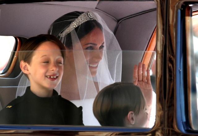 Cô dâu Meghan Markle lộng lẫy trong bộ váy cưới màu trắng trơn và phủ khăn voan dài, ngồi trong xe ô tô vẫy chào người hâm mộ.