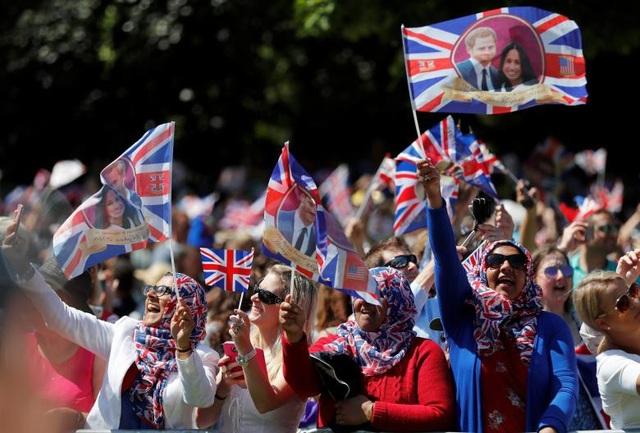 Rất đông người dân Anh tập trung hai bên đường chờ đợi xe cô dâu đi qua.