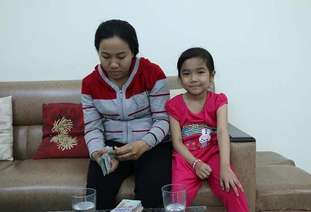 Mẹ con chị Thắm nhận tiền của bạn đọc báo Dân trí hỗ trợ