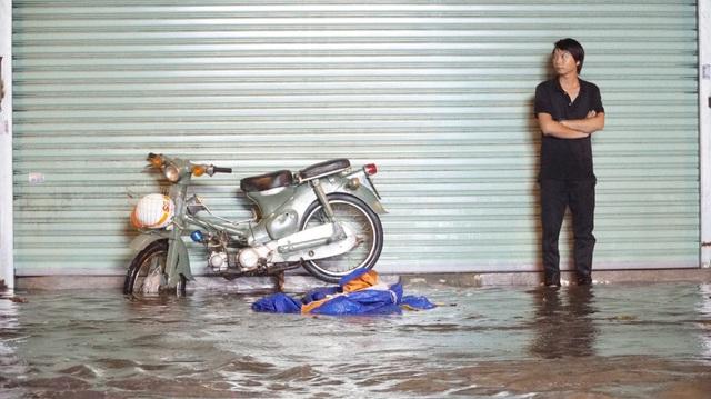 Một thanh niên dẫn xe lên bờ đợi nước rút rồi mới về nhà