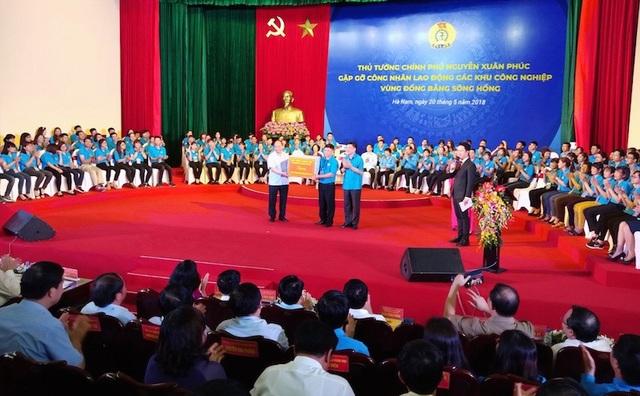 Thủ tướng Chính phủ Nguyễn Xuân Phúc và Chủ tịch TLĐLĐVN tặng bộ máy vi tính cho công nhân Vũ Xuân Đạt.