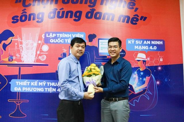 Đại diện nhà trường tặng hoa cho anh Phan Văn Quyền (bên phải).