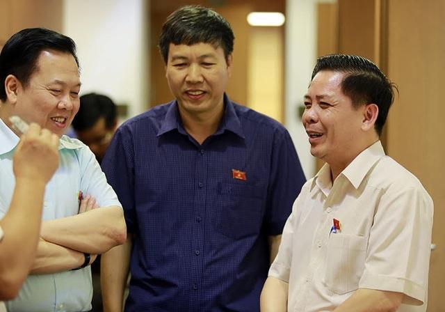 Bộ trưởng GTVT Nguyễn Văn Thể (phải) trao đổi với các đại biểu bên lề phiên thảo luận sáng 22/5 (ảnh: Như Phúc)
