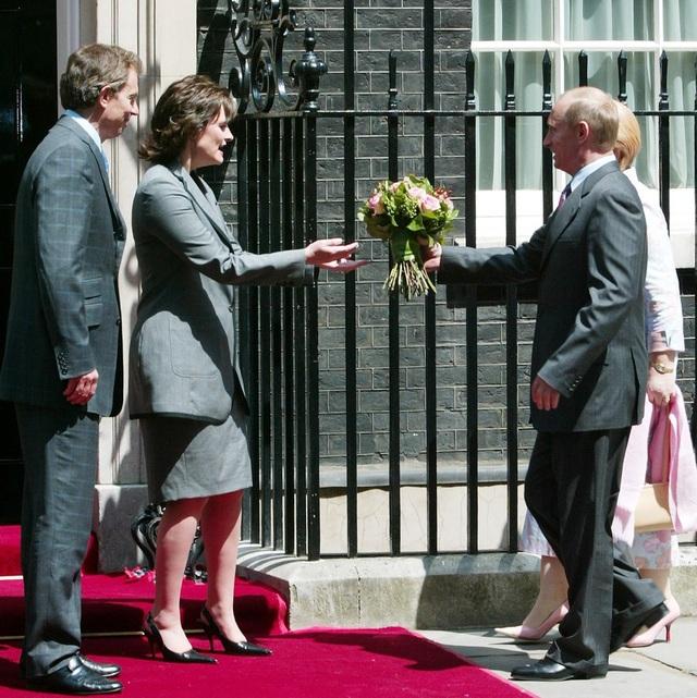 Ông Putin mang theo một bó hoa để tặng bà Cherie Blair, phu nhân cựu Thủ tướng Anh Tony Blair, ngay trước mặt chồng bà. (Ảnh: Reuters)