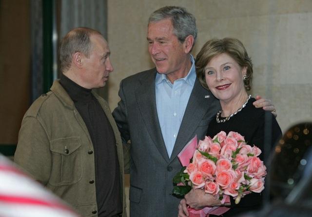 Bà Laura Bush, vợ cựu Tổng thống Mỹ George W. Bush, ôm bó hoa hồng do ông Putin tặng. (Ảnh: Sputnik)
